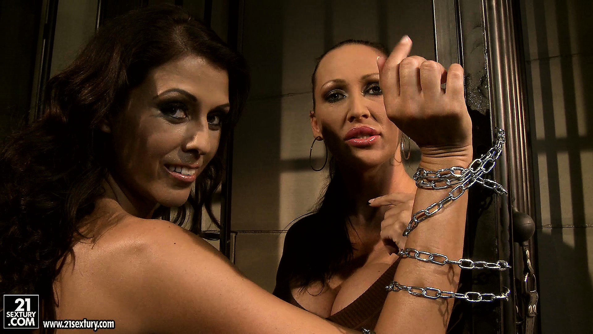 Porno Video of Mandy Gets Claudia Chained Up Against The Bars And Whips Her Butt